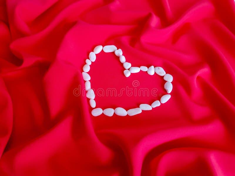 Modèle, texture, fond, papier peint Le grand coeur fait de petites pierres blanches est sur le fond du tissu de corail saturé image libre de droits