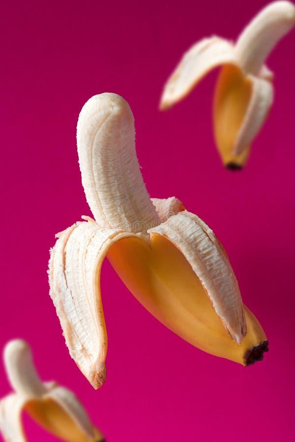 Modèle volant de bananes sur un fond rose vibrant image libre de droits