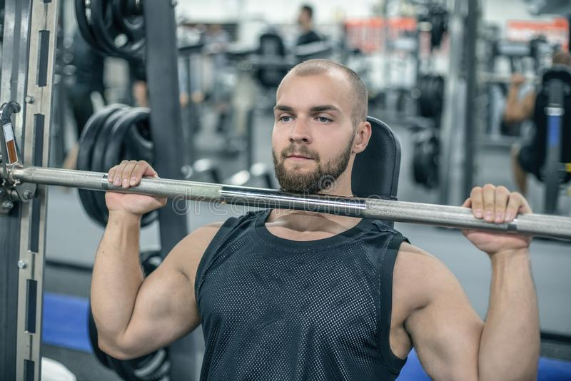 Modèle volontaire de forme physique de jeune homme occupé avec un barbell dans le simulateur de Smith dans le gymnase Concept des images stock