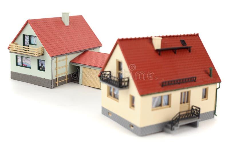 Modèles de deux maisons avec le garage pour le véhicule sur le blanc image stock