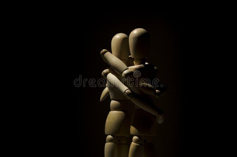 Modèles en bois de mannequin embrassant avec le fond foncé image libre de droits