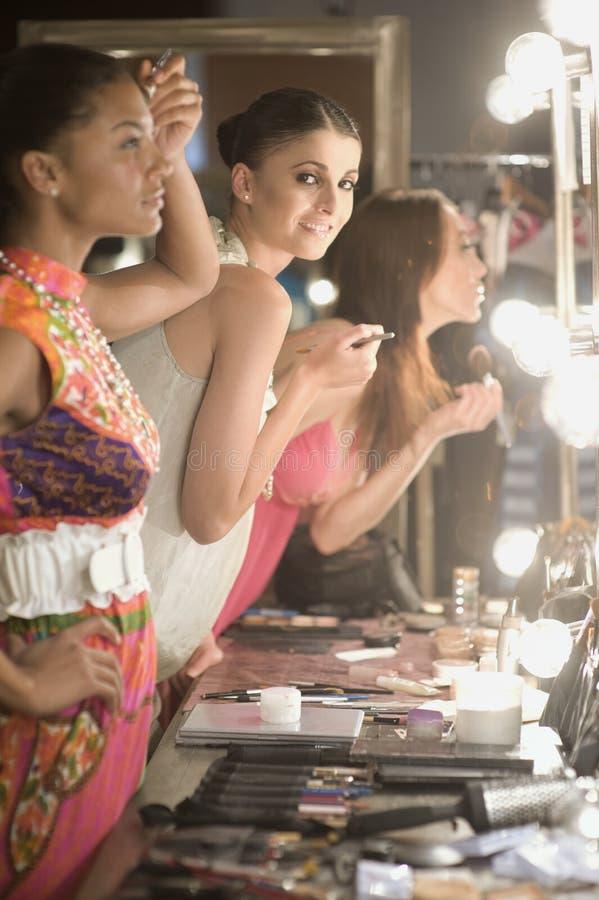 Modèles multi-ethniques appliquant le maquillage dans le miroir de vestiaire images stock
