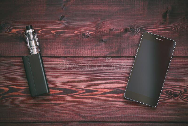 MOD del E-cig o cigarrillo electrónico para el teléfono móvil vaping y elegante en un de madera foto de archivo