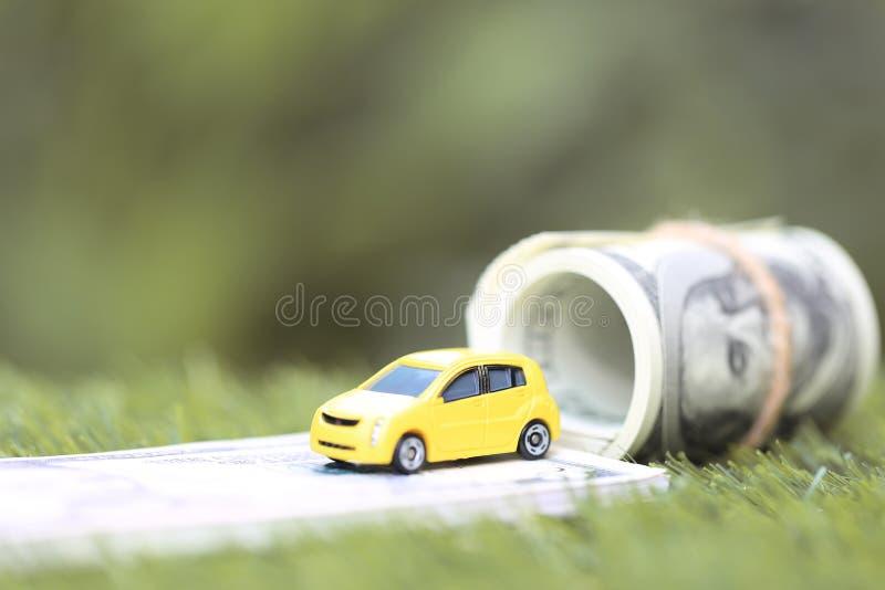 Mod?le jaune miniature de voiture avec des billets de banque de dollas sur le fond de vert de nature, l'argent ?conomisant pour l images stock