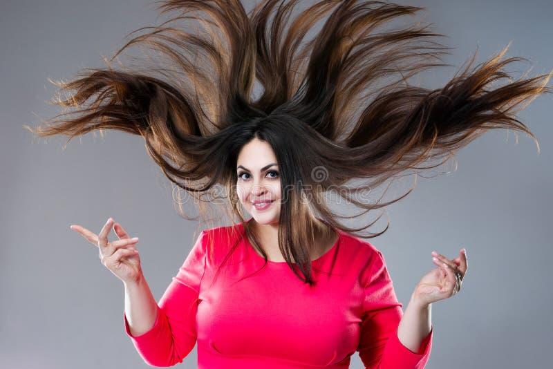 Mod?le plus de taille avec les longs cheveux soufflant dans le vent, grosse femme de brune sur le fond gris, concept positif de c photo libre de droits