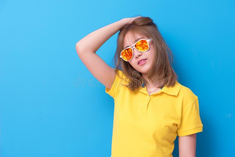 Moda asi?tica de la mujer que presenta con los vidrios del ojo de la moda en el fondo azul Mujer que lleva el polo amarillo y ama imagen de archivo