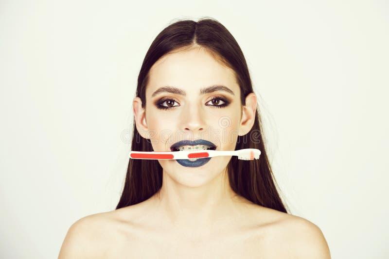 Moda, belleza y concepto femeninos del anuncio la muchacha con los apoyos y el cepillo de los dientes, tiene maquillaje de moda fotos de archivo