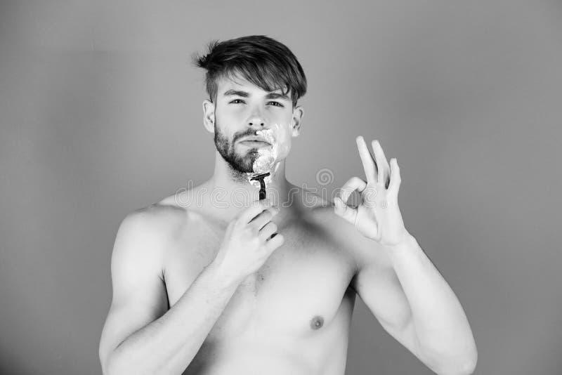 Moda, belleza y concepto masculinos del anuncio Hombre joven con la cara afeitada mitad que muestra gesto aceptable fotografía de archivo libre de regalías