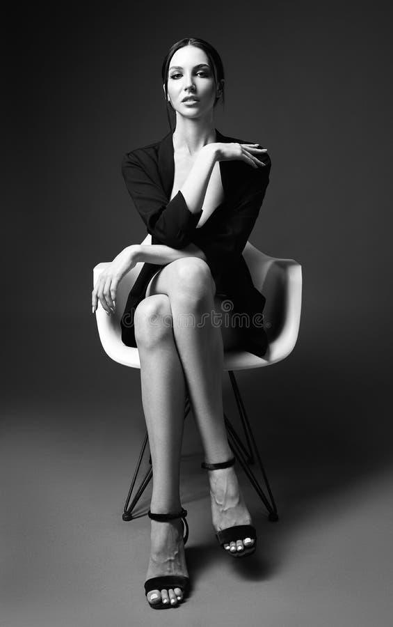 Moda del estudio tirada de la mujer joven magn?fica que se sienta en silla Retrato de la muchacha hermosa vestido en chaqueta y s fotografía de archivo libre de regalías