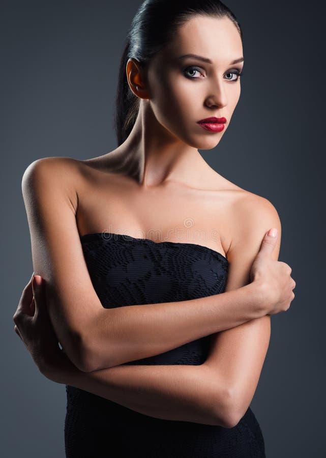 Moda del estudio tirada: mujer joven atractiva vestida en negro foto de archivo libre de regalías