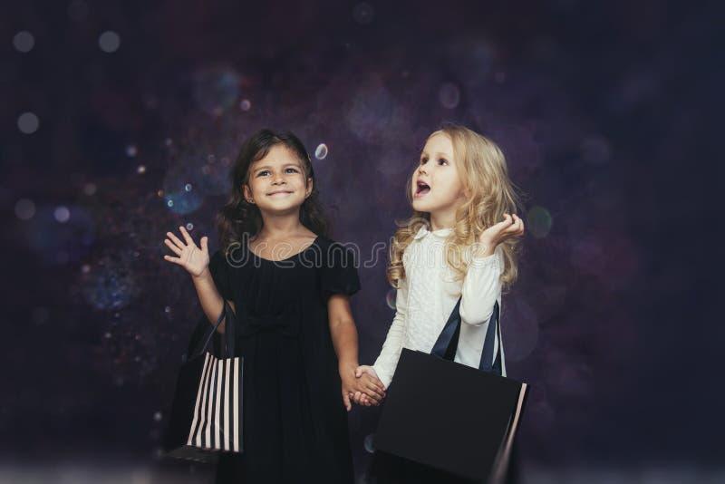 Moda del niño de las niñas con las bolsas de papel en un fondo con fotografía de archivo libre de regalías