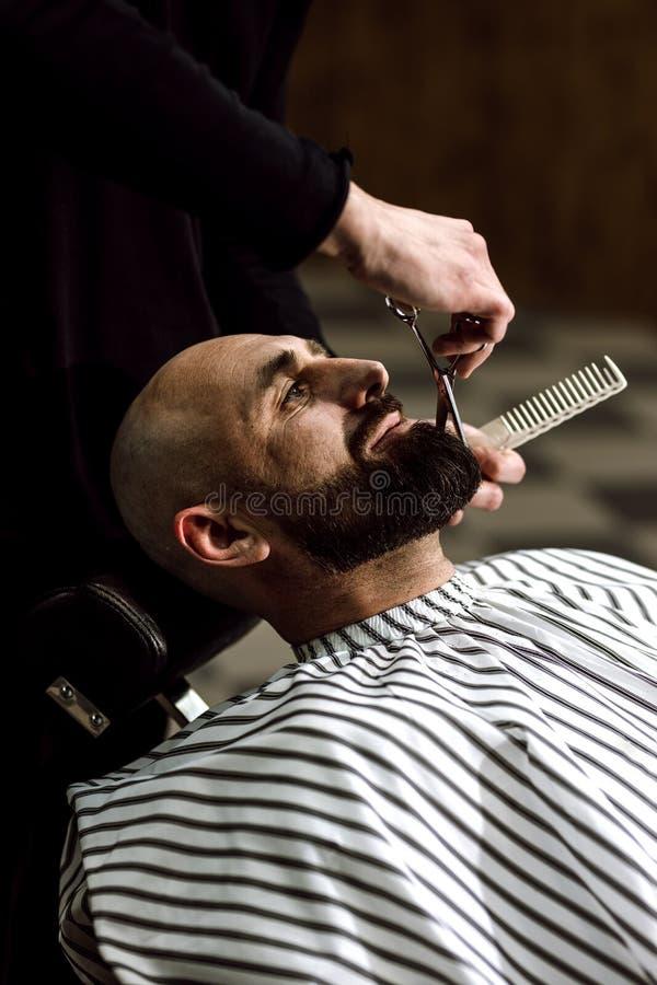 Moda del ` s de los hombres La barba de las tijeras del peluquero del hombre brutal en la barbería elegante imagenes de archivo