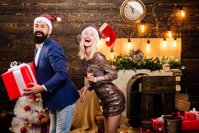 Moda del traje del hombre de la Navidad Pares en amor Las muchachas bebidas celebran A?o Nuevo Interior casero de la Navidad Muje foto de archivo libre de regalías