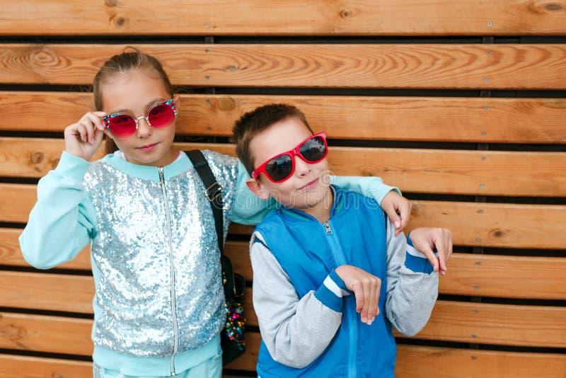 Moda dzieciaki w miasto stojakach na drewnianej ścianie obraz stock