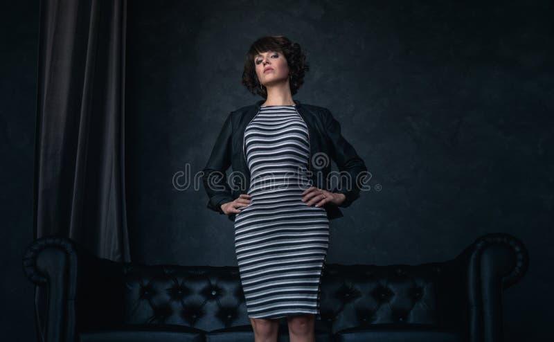 Moda: Dziewczyna w długiej pasiastej skórzanej kurtce i sukni stoi w czarnym pokoju z czarną rzemienną kanapą patrzeje obraz royalty free