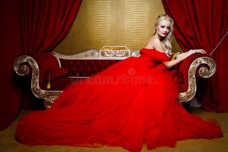 Moda krótkopęd piękna blond kobieta w długim czerwieni sukni obsiadaniu na sof zdjęcia royalty free