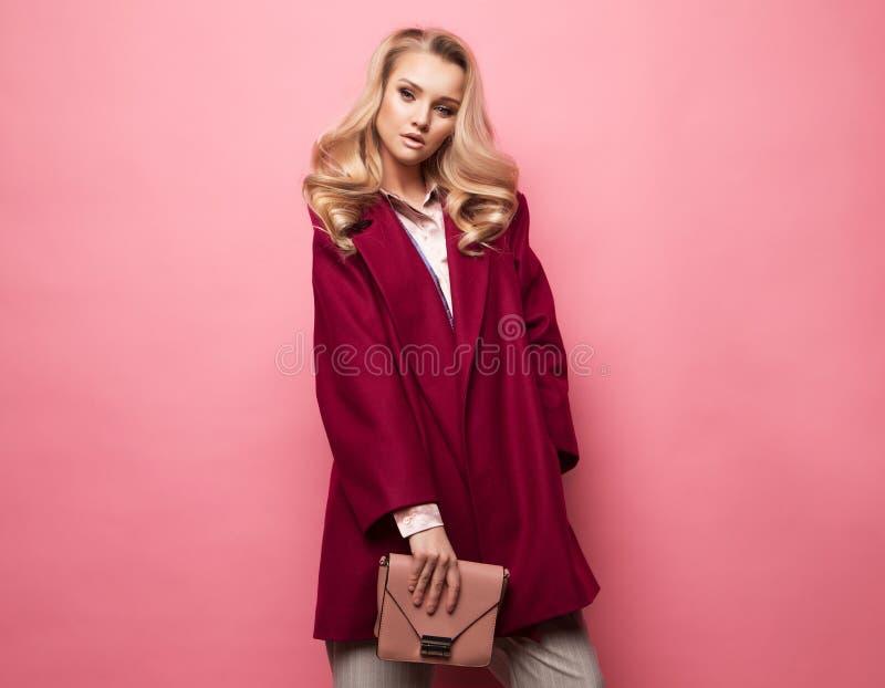 Moda, ludzie i stylu życia pojęcie: Pięknej kobieta kędzierzawego włosy długiej blond odzieży kaszmirowy żakiet i mienie torebka fotografia royalty free