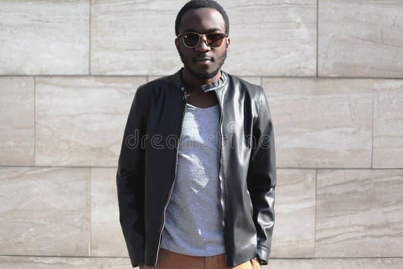 Moda mężczyzna afrykański być ubranym okulary przeciwsłoneczni i czerni rockowa skórzana kurtka nad textured szarym tłem w mieści fotografia stock