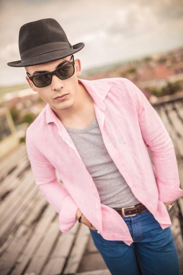 Moda młodego człowieka pozycja z rękami w kieszeniach fotografia stock