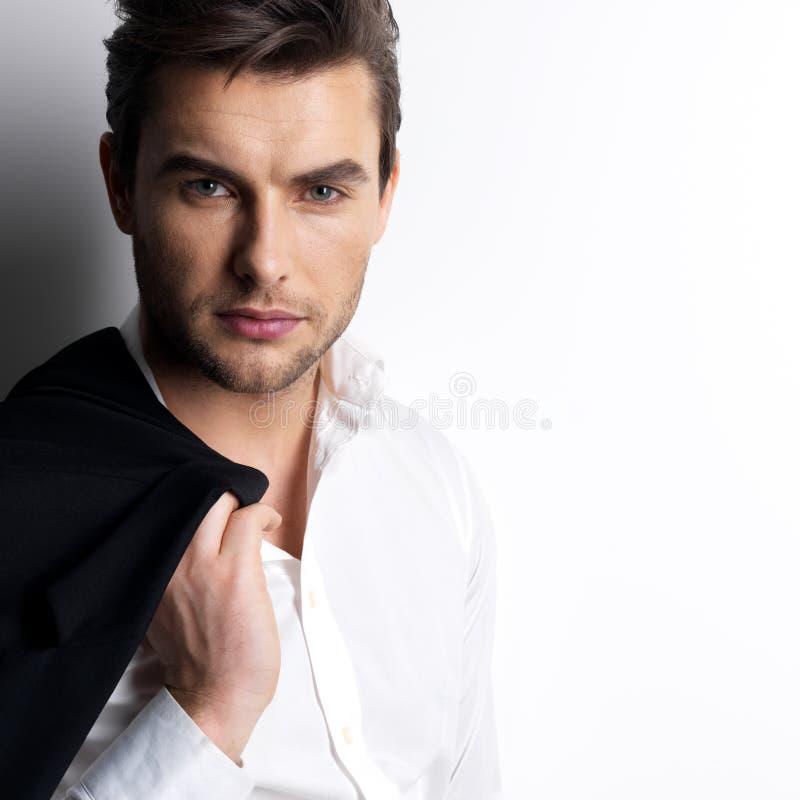Moda młody człowiek w białej koszula trzyma czarną kurtkę zdjęcie royalty free