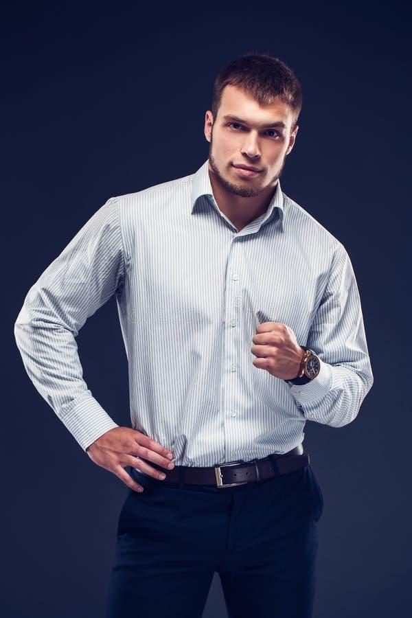 Moda młody poważny mężczyzna w obdzierającej koszula zaciska jeden ` s rękę i patrzeć kamerę w pięść zdjęcia royalty free
