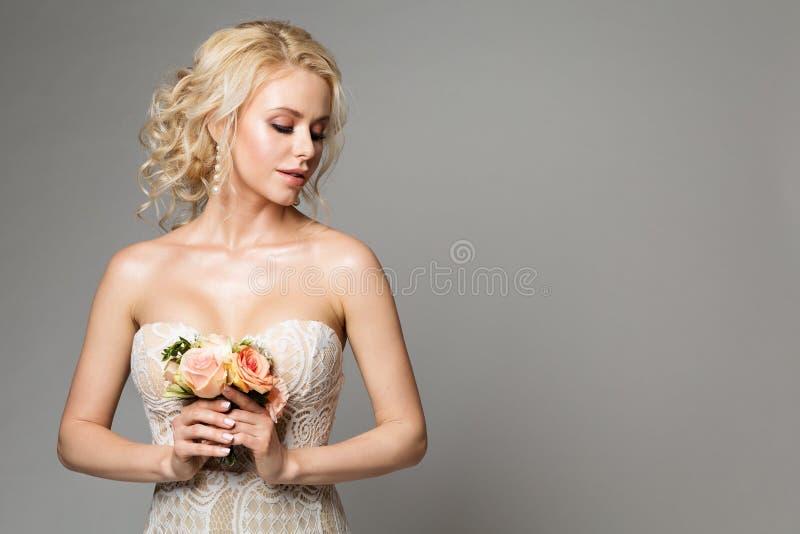 Moda modelów portret z kwiatu bukietem, Pięknym kobiety panny młodej Makeup i fryzurą, dziewczyny studio strzelał na szarość zdjęcie stock