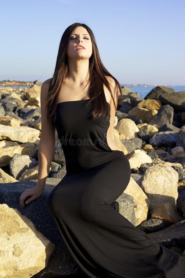 Moda model z czerni sukni obsiadaniem na skałach przed morzem zdjęcie royalty free