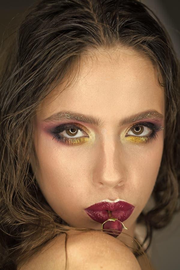 Moda model z długim brunetka włosy, fryzury kobieta z czerwieni różą w usta, kobieta dzień Piękno dziewczyna z splendoru spojrzen zdjęcia royalty free