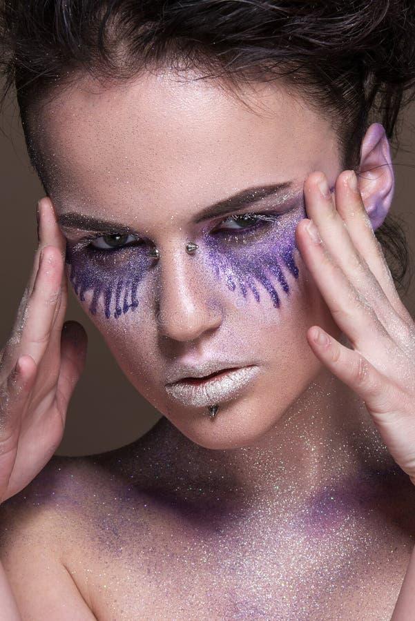 Moda model z kolorowym makijażem i błękitną błyskotliwością i błyska na jej ciele i twarzy obrazy stock