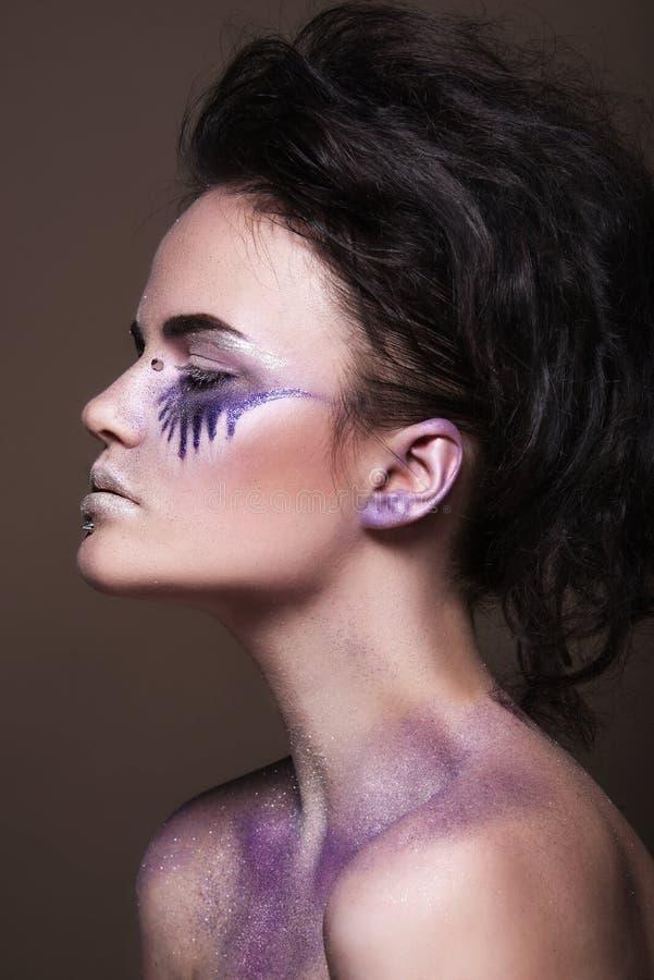 Moda model z kolorowym makijażem i błękitną błyskotliwością i błyska na jej ciele i twarzy obraz royalty free