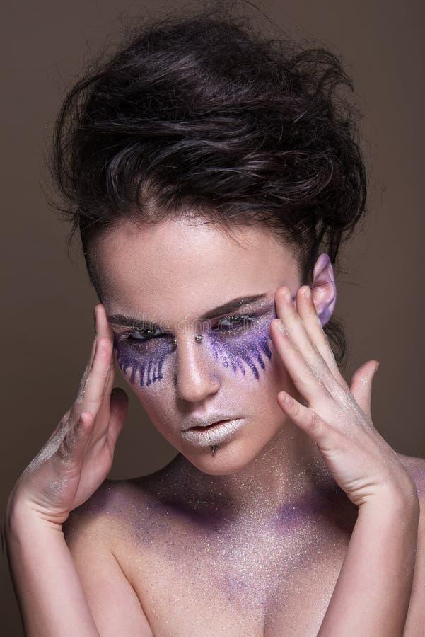 Moda model z kolorowym makijażem i błękitną błyskotliwością i błyska na jej ciele i twarzy fotografia stock