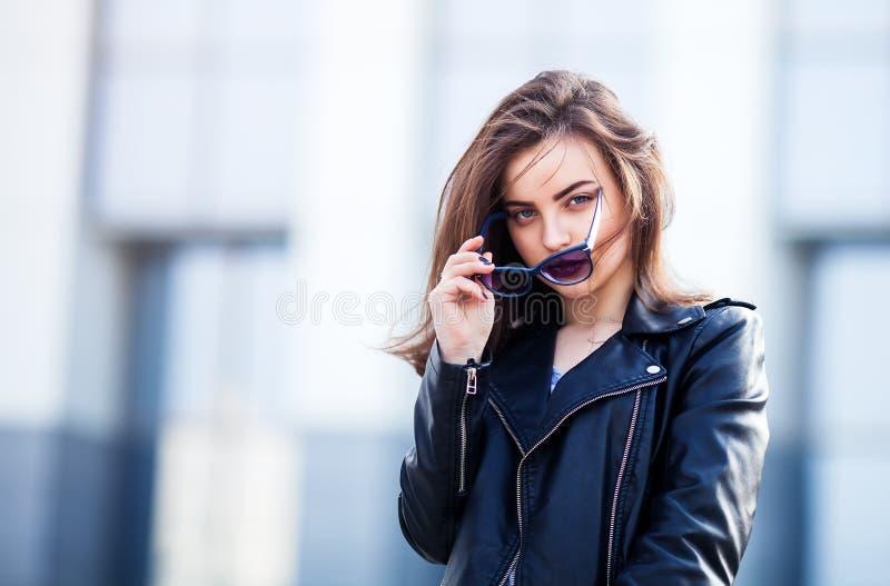 Moda modnisia kobiety pozować plenerowy skórzana kurtka, brunetka włosy, jaskrawe czerwone wargi, okulary przeciwsłoneczni Uliczn obraz stock