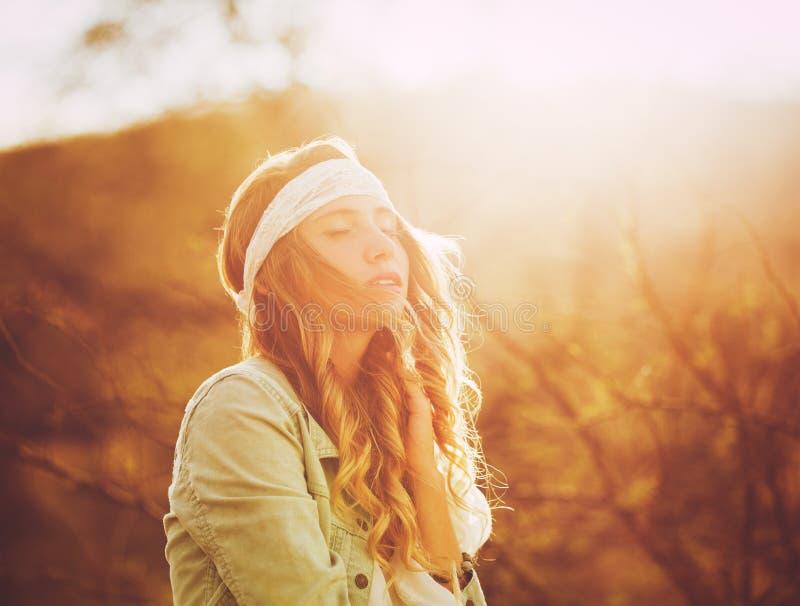 Moda, mujer joven al aire libre en la puesta del sol imagenes de archivo