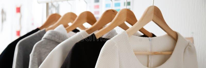 Moda popielatego bielu odzieżowi wyborowi biali colours na drewnianych wieszakach obraz stock