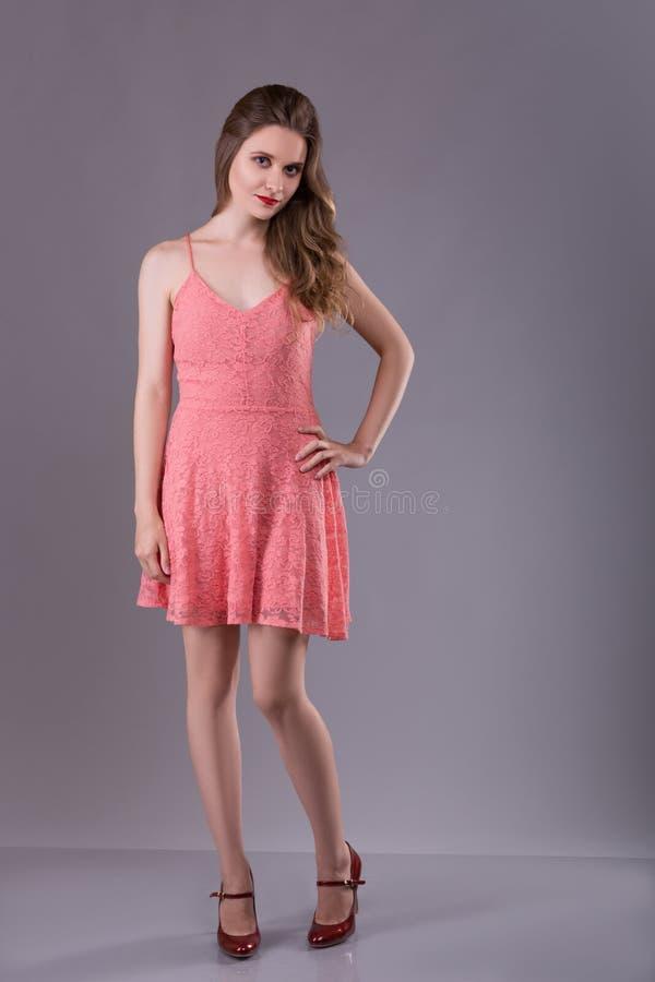 Moda portret kobieta Perfect makijaż Dziewczyna w menchii sukni na szarym tle obrazy royalty free
