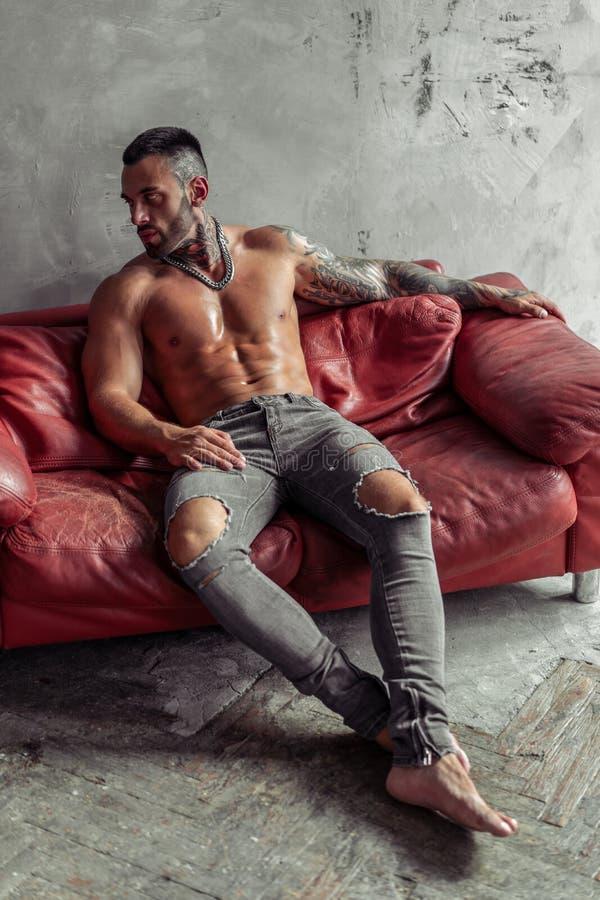 Moda portret Seksowny nagi samiec model z tatuażem i czarny brody obsiadanie w gorącej pozie na czerwonej rzemiennej kanapie Loft obraz royalty free