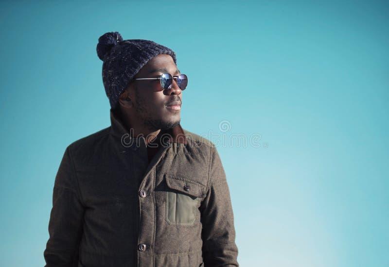 Moda portreta afrykański mężczyzna jest ubranym okulary przeciwsłonecznych, kurtka, trykotowy kapelusz w zima dniu nad niebieskie zdjęcia royalty free