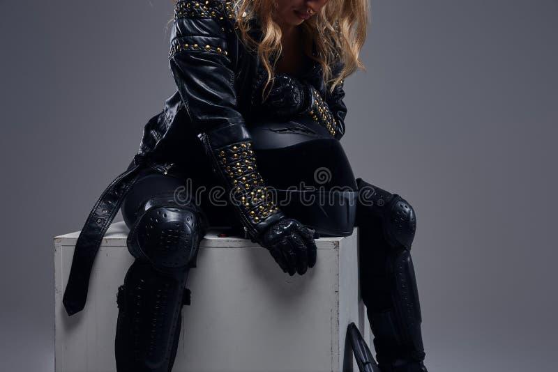 Moda, sport, ekstremum Cropped wizerunek rowerzysta dziewczyna jest ubranym motocykl przekładni obsiadanie na szarym pudełku w st obrazy royalty free