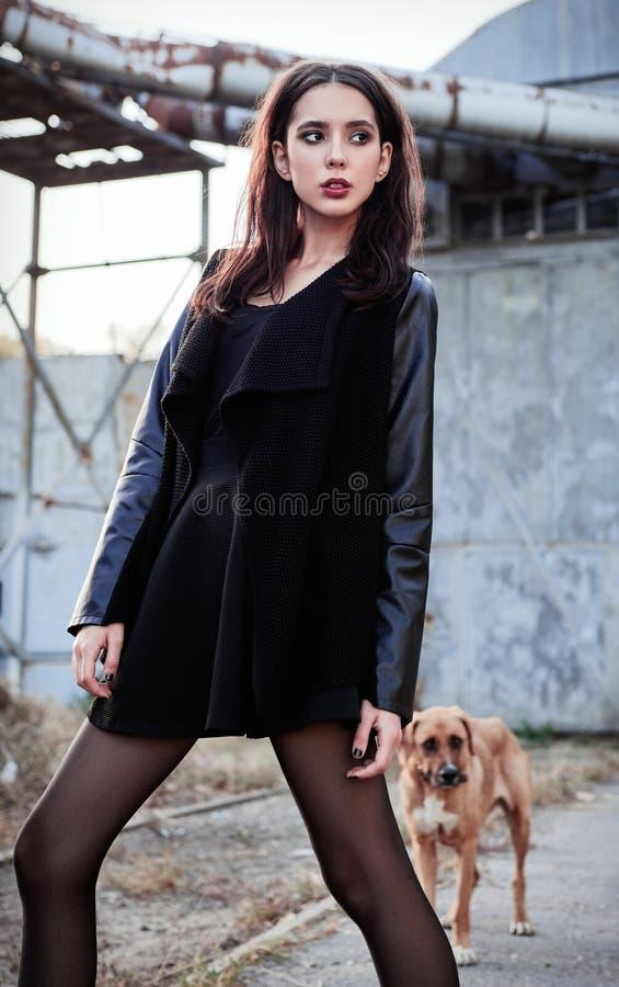 Moda strzelająca: pięknej rockowej dziewczyny nieformalny model ubierał w czarnej kurtki i psa pozycji przy przemysłowym miejscem obrazy royalty free