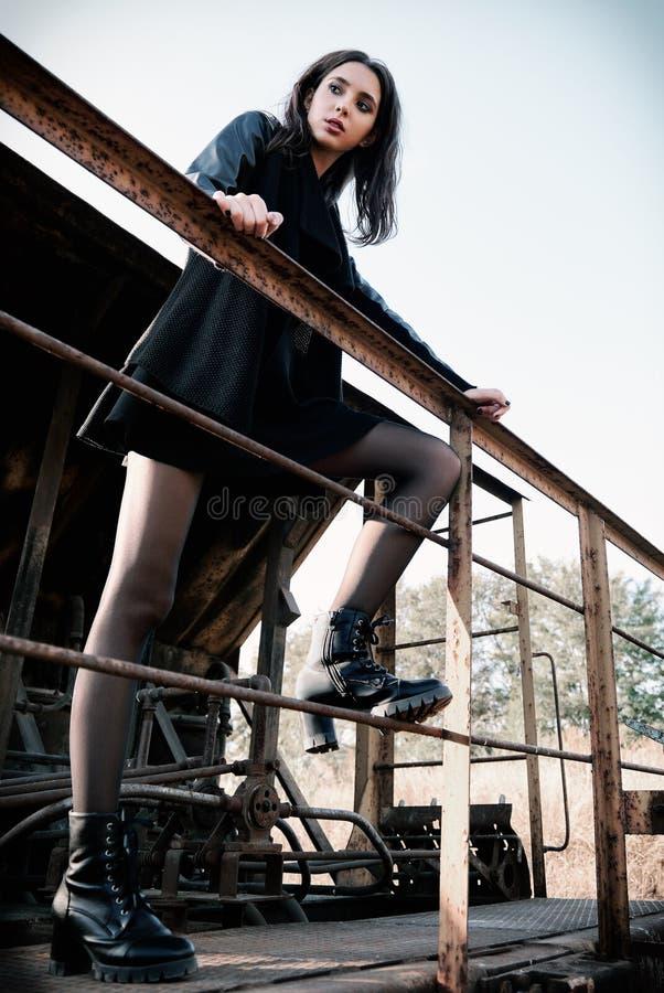 Moda strzelająca: portret ładnej rockowej dziewczyny nieformalny model ubierał w czarnej kurtki i spódnicy pozycji na taborowym s obrazy stock