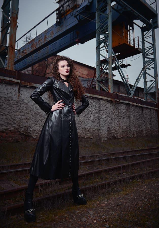 Moda strzelająca: portret ładnej rockowej dziewczyny nieformalny model w rzemiennej żakiet pozycji przy linia kolejowa parkiem pr obrazy stock