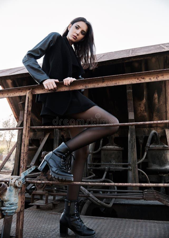 Moda strzelająca: portret ślicznej rockowej dziewczyny nieformalny model ubierał w czarnej kurtki i spódnicy pozycji na taborowym fotografia stock