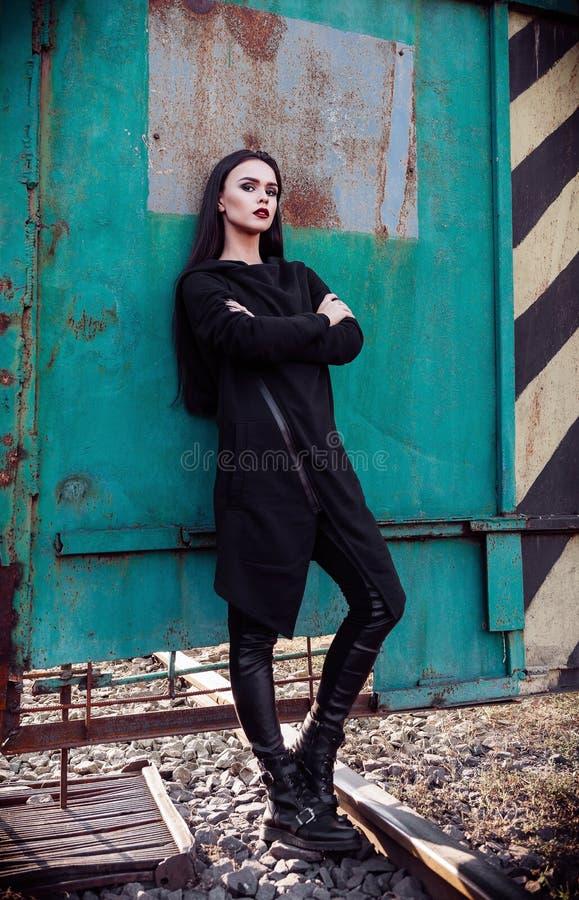 Moda strzelająca: portret ślicznej rockowej dziewczyny nieformalny model w tunice i skórze dyszy pozycję w przemysłowym terenie obraz stock