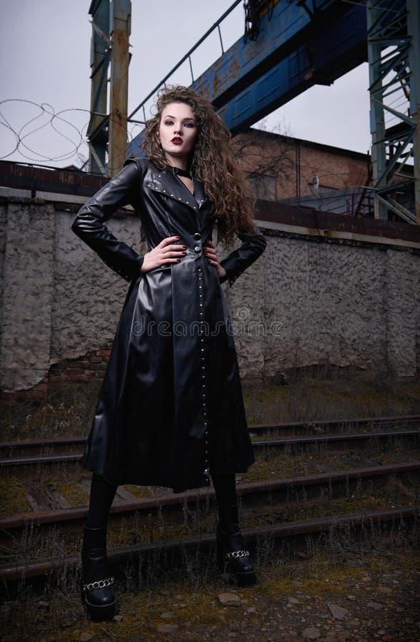 Moda strzelająca: portret chłodno rockowej dziewczyny nieformalny model w rzemiennej żakiet pozycji przy linia kolejowa parkiem p obrazy royalty free