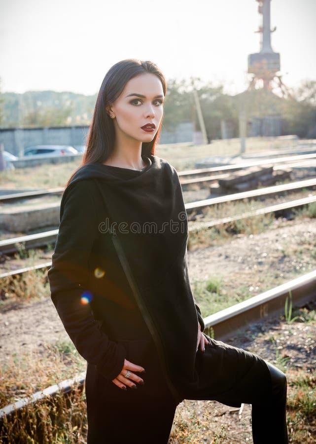 Moda strzelająca: portret pięknej rockowej dziewczyny nieformalny model w tunice i spodnia stoi przy linia kolejowa przemysłowym  fotografia stock