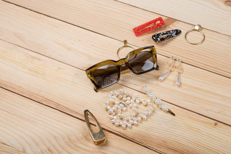 Moda wykazuje tendencj? akcesoria - okulary przeciws?oneczni i bi?uteria: pere?kowa kolia, w?osy per?y klamerka, z?oci?ci kolczyk obraz stock