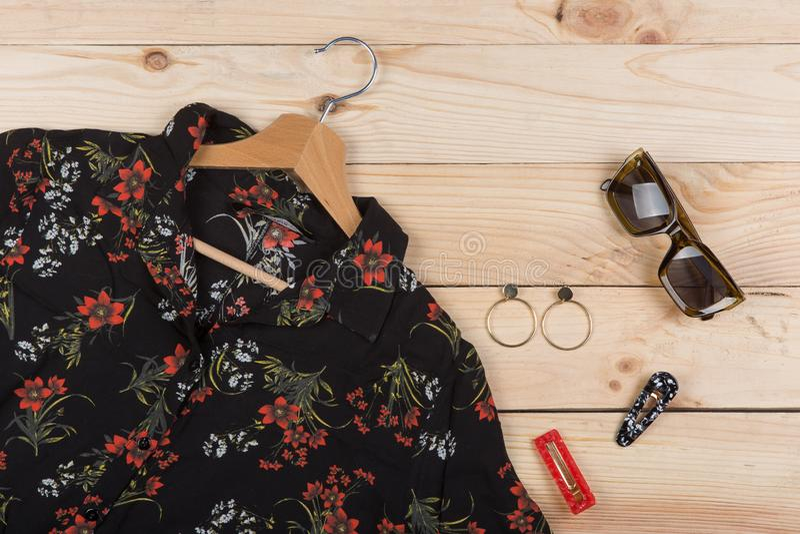 Moda wykazuje tendencj? okulary przeciws?onecznych, bluzk? w kwiecistym druku na wieszaku i bi?uteri? -: kolorowy barrette, kolcz zdjęcie royalty free