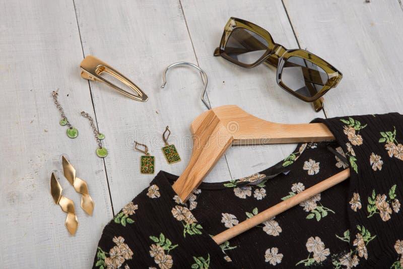 Moda wykazuje tendencj? okulary przeciws?onecznych, czerni sukni? w kwiecistym druku na wieszaku i bi?uteri? -: barrette, srebra  obrazy stock