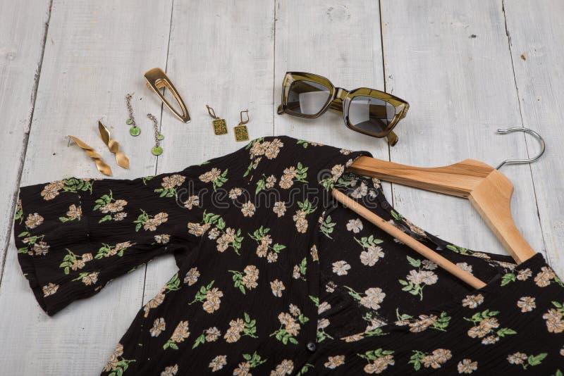 Moda wykazuje tendencj? okulary przeciws?onecznych, czerni sukni? w kwiecistym druku na wieszaku i bi?uteri? -: barrette, srebra  fotografia stock