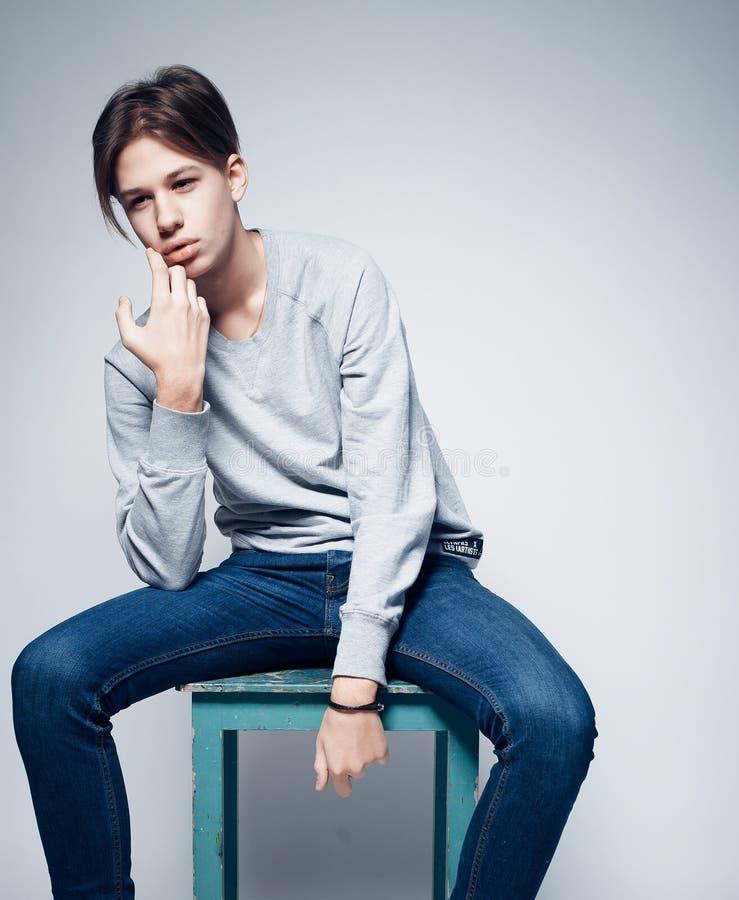 Moda y concepto de la gente: hombre joven de moda elegante vestido en la ropa casual que presenta en fondo encima gris foto de archivo libre de regalías